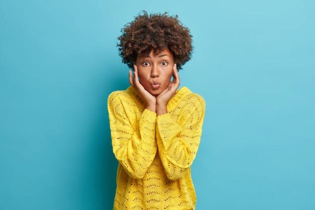 Półdługie ujęcie pięknej młodej kobiety afroamerykańskiej delikatnie dotyka twarzy, trzyma usta złożone, ma delikatny wygląd, nosi swobodny żółty sweter z dzianiny odizolowany na niebieskiej ścianie, chce kogoś pocałować
