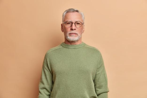 Półdługie ujęcie poważnego brodatego mężczyzny wygląda na pozbawionego emocji z przodu z surowym wyrazem twarzy, nosi okulary, a sweter ma siwe włosy, pewny siebie w czymś odizolowanym na beżowej ścianie studia