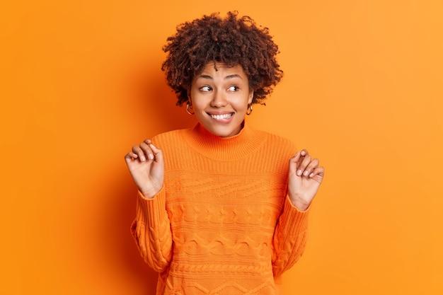Półdługie ujęcie pozytywnej afroamerykanki gryzie usta z uniesionymi rękoma odwraca wzrok uśmiechy zaciekawione zauważa coś interesującego nosi swobodny sweter rozpięty na pomarańczowej ścianie