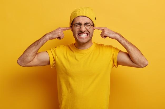 Półdługie ujęcie zdenerwowanego faceta zaciska zęby, zatyka uszy palcami wskazującymi, ignoruje irytujące dźwięki, odczuwa ból lub ból ucha