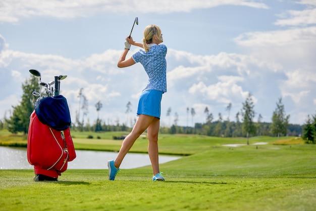 Pole golfowe, piękna dziewczyna przygotowuje się do uderzenia piłki. koncepcja stylu życia, koncepcja golfa, dążenie do doskonałości, kunszt, sport królewski.