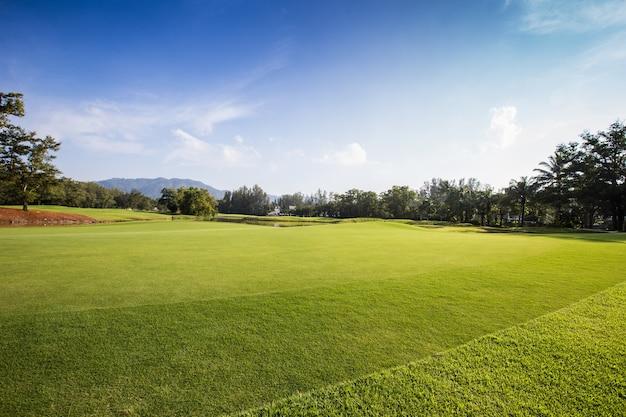 Pole golfowe z zielonym polem i niebieskim tłem nieba
