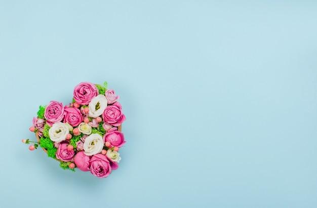 Pole kształt serca kwiat na niebieskim tle z pustym miejscem na tekst. widok z góry, płaski układ.