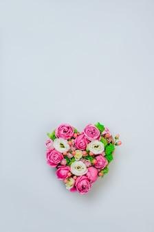 Pole kształt serca kwiat na szarym tle z pustym miejscem na tekst. widok z góry, płaski układ.