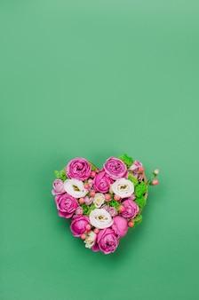 Pole kształt serca kwiat na zielonym tle z pustym miejscem na tekst. widok z góry, płaski układ.