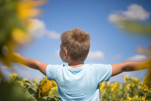 Pole szczęśliwe dziecko pojęcie wolności i szczęścia na zewnątrz słonecznika. dziecko zabawy w zielonym polu wiosny na tle błękitnego nieba. koncepcja zdrowego i aktywnego stylu życia