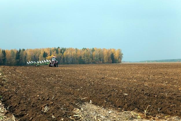 Pole uprawne, które jest przetwarzane przez traktor. zaorany