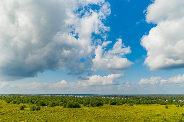 Pole z białymi chmurami na niebieskim niebie latem