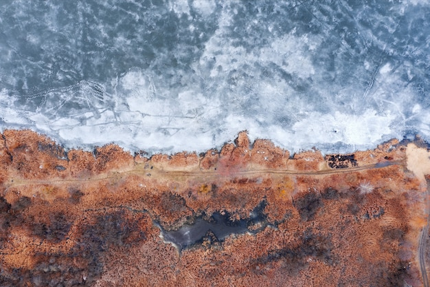 Pole z pomarańczową trawą w pobliżu zamarzniętego jeziora pokrytego lodem