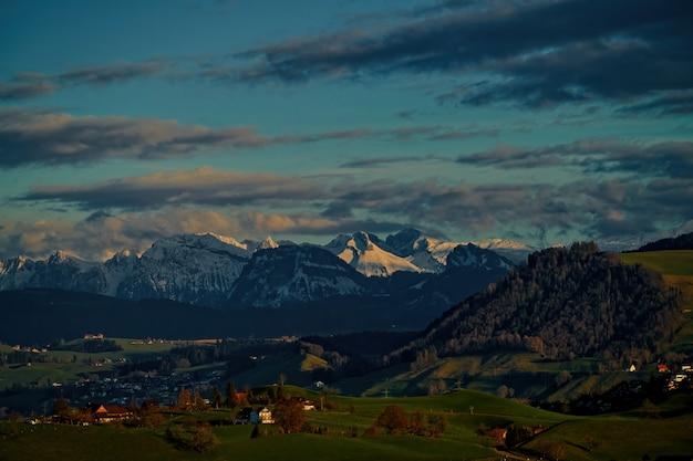 Pole zielona trawa w pobliżu góry pod zachmurzonym niebem w ciągu dnia
