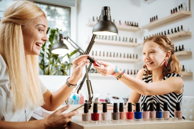 Polecam kolor. pomocna śliczna nastoletnia córka polecająca matce kolor lakieru do paznokci