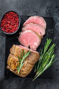 Polędwica rostbef mięso z polędwicy na marmurowej desce. czarne tło. widok z góry.