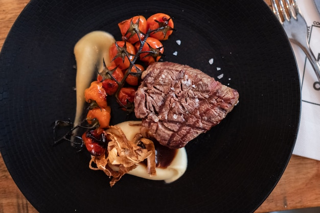 Polędwica wołowa z rustykalnymi tłuczonymi ziemniakami, pieczonymi wiśniami i sosem czosnkowym confit na ciemnym talerzu