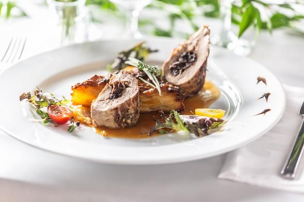 Polędwiczki wieprzowe faszerowane śliwkami, redukcja z czerwonego wina z gratin ziemniaczanym. kreatywne świąteczne danie główne serwowane na weselu lub innej uroczystości.
