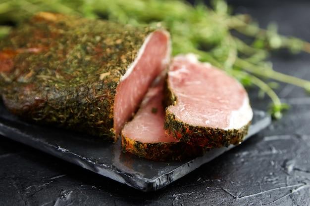 Polendwitz to suszona polędwica, suszona wieprzowina z przyprawami i świeżym zielonym tymiankiem, deska do krojenia łupków na czarnym stole