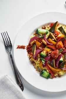 Polenta z duszonymi warzywami na lekkim talerzu, danie z kaszy kukurydzianej z gulaszem warzywnym, widok z góry na tradycyjne dania kuchni włoskiej, miejsce.