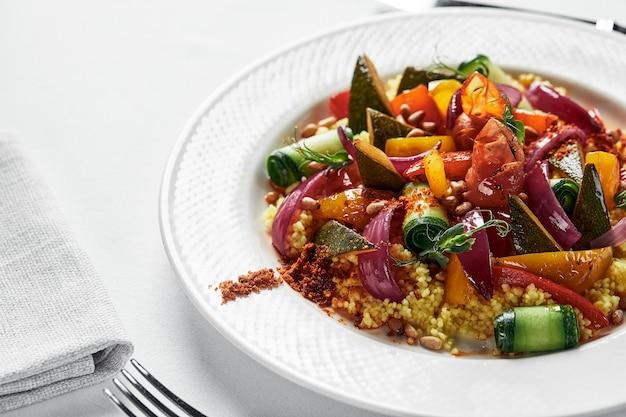 Polenta z warzywami z bliska, danie z mąki kukurydzianej z warzywami na białym talerzu, jasnym tle.