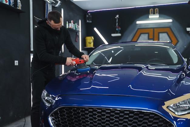 Polerowanie samochodu po malowaniu. detalowanie samochodu z zewnątrz. urządzenie do polerowania w dłoniach