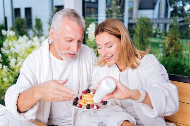 Polewa waniliowa. troskliwa blondynka pomaga swojemu brodemu mężowi w nakładaniu waniliowej polewy na naleśniki