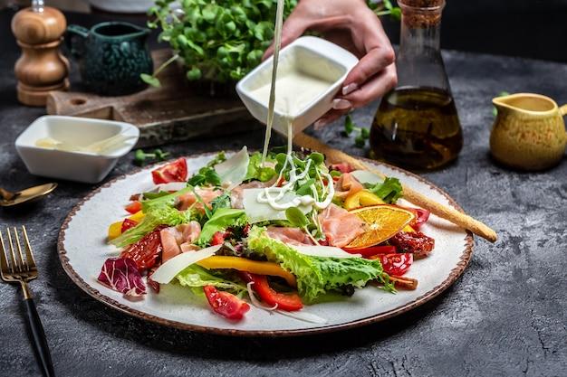Polewanie białym sosem na talerz gotowanej sałatki z kawałkami wędzonego łososia, sałatą, suszonymi pomidorami i ziołami, zdrowa żywność. menu dietetyczne,