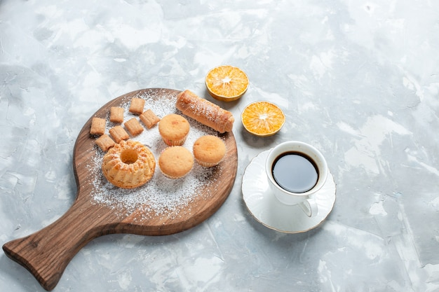 Półgórny pyszny bajgiel z filiżanką herbaty i ciasta na jasnobiałym tle.