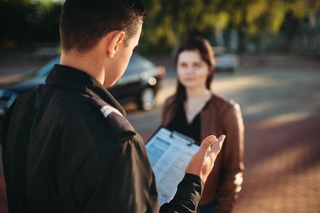 Policjanci czytają prawo kobiecie kierowcy