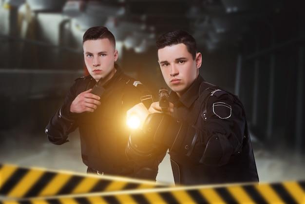 Policjanci z bronią i latarnią, widok z przodu