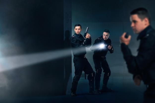 Policjanci z bronią ubrani w mundury i kamizelki kuloodporne
