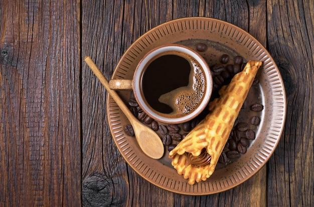 Policjant gorącej kawy i rożków waflowych ze skondensowanym mlekiem w talerzu na starym drewnianym stole, widok z góry