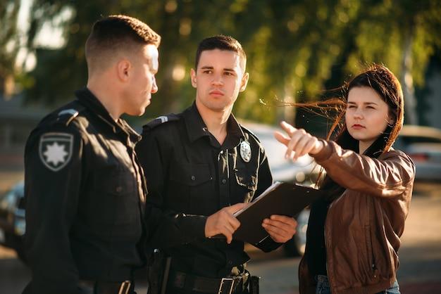 Policjant pisze zeznania kobiety kierowcy