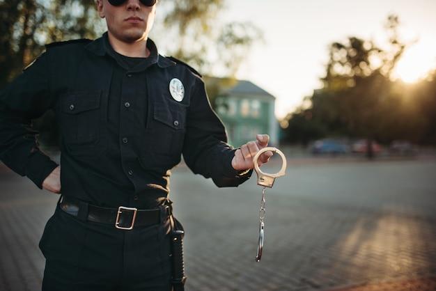 Policjant trzyma w rękach kajdanki