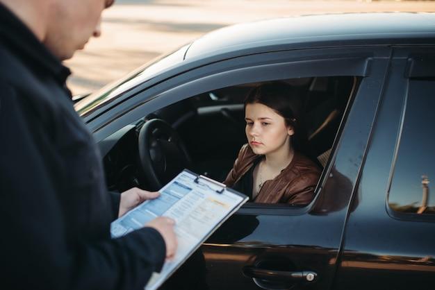 Policjant w mundurze pisze grzywnę do kierowcy