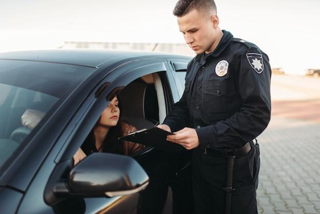 Policjant w mundurze sprawdza prawo jazdy kobiety-kierowcy