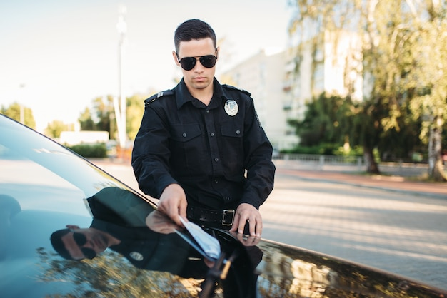 Policjant w mundurze wypisuje mandat na drodze