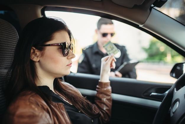 Policjant w mundurze wystawia mandat kobiecie kierowcy
