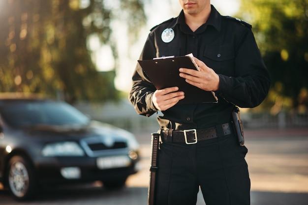Policjant z notatnikiem w rękach sprawdza samochód
