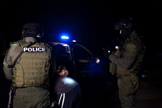Policjant zakłada kajdanki na ręce przestępcy podczas zatrzymania. samochód policyjny z migającymi latarniami morskimi. rozmyty