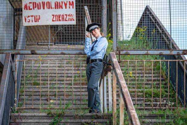 Policjantka na schodach pisze po czesku niedozwolone wejście zabronione