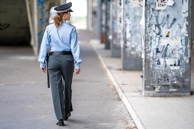 Policjantka w mundurze spacerująca po dzielnicy miasta