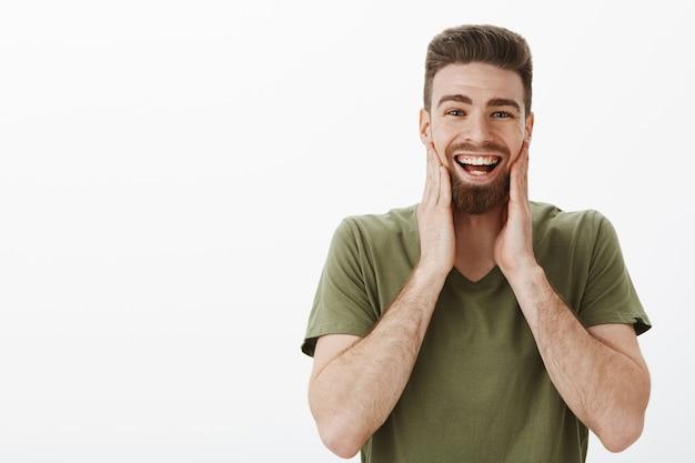 Policzki bolały od śmiechu i uśmiechu. portret rozbawionego, szczęśliwego, optymistycznego, atrakcyjnego, brodatego dorosłego mężczyzny w oliwkowej koszulce, dotykającego twarzy i uśmiechającego się, bawiącego się w świetnym nastroju na białej ścianie
