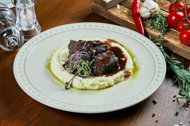 Policzki cielęce smażone w sosie teriyaki z przystawką tłuczonych ziemniaków w białej misce na drewnianym stole. jedzenie w restauracji. kuchnia ukraińska. leżał płasko, z bliska