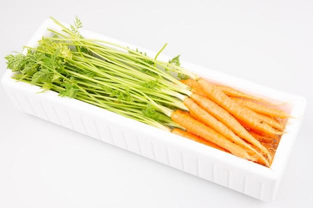 Polistyrenowe białe pudełko przemysłowe z drobnymi marchewkami na sprzedaż na białym tle