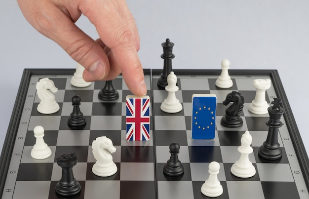 Polityka rąk podnosi figurę flagą wielkiej brytanii gra polityczna i strategia szachowa brexit