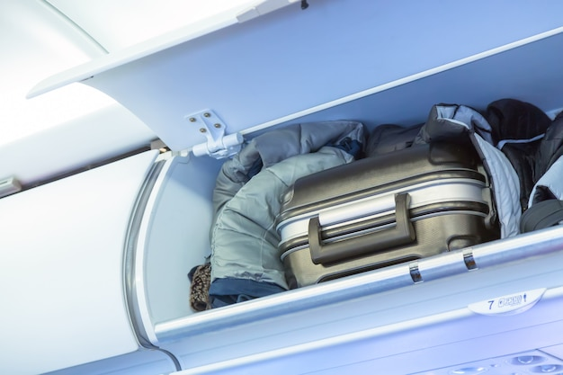 Półka bagażowa z walizką bagażową w samolocie