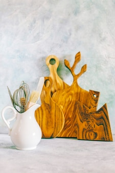 Półka kuchenna z różnymi ziołami, przyprawami, nasionami, roślinami strączkowymi, deskami do krojenia, naczyniami na białej powierzchni