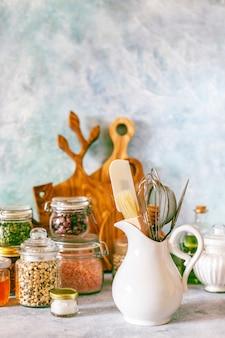 Półka kuchenna z różnymi ziołami, przyprawami, nasionami, roślinami strączkowymi, deskami do krojenia