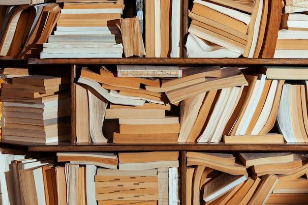 Półka różne wiele starych książek w tle biblioteki sklep losowo rozrzucone bałagan