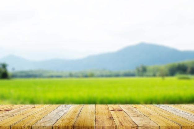 Półka z brązowej deski z drewna z niewyraźną zieloną farmą ryżu z naturą górską i chatową.