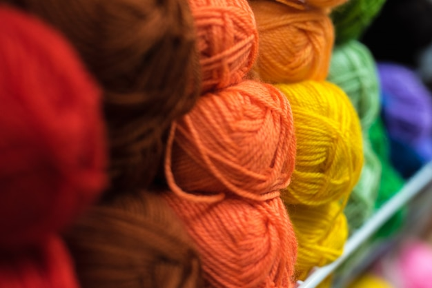 Półka z dużą ilością kolorowej przędzy do robienia na drutach. wybór kolorowej wełny przędzy w witrynie sklepowej