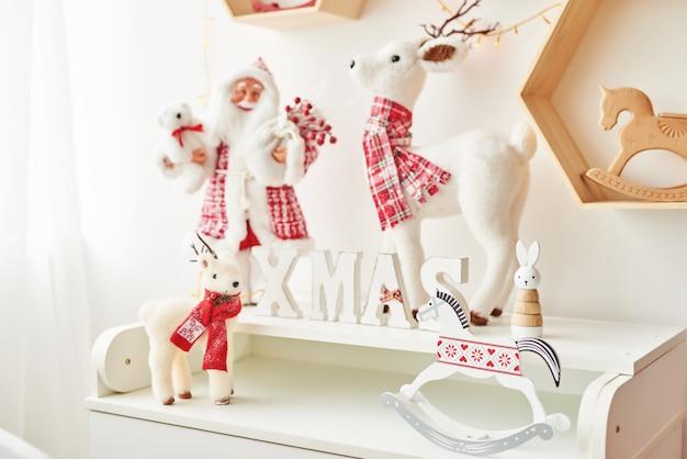 Półka z figurkami świątecznymi święty mikołaj i jeleń w pokoju dziecięcym. świąteczne wnętrze sypialni dla dzieci